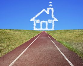 image of track home  - House shape clouds in blue sky with dark red running track and grass - JPG
