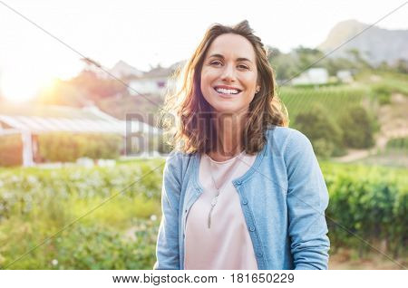 poster of Cheerful mature woman enjoying in park during sunset. Happy hispanic woman in casual feeling relaxed