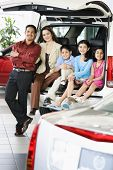 Hispanic family at car dealership poster