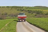 stock photo of spreader  - an english landscape with a tractor with fertilzer spreader attached travelling along a quiet country road in the yorkshire wolds - JPG