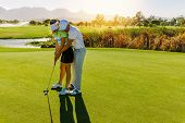 Male Instructor Showing Woman To Play Golf poster