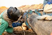 picture of pipe-welding  - Pipeline welder working on construction site wearing safety clothing - JPG