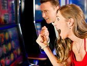 picture of slot-machine  - Couple in Casino on a slot machine - JPG