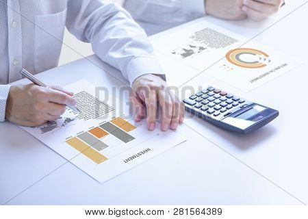 poster of Businessmen Or Analyst In A Meeting Room Partially Cropped At Hands Holding A Pen On An Investment R