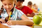 stock photo of youngster  - Portrait of lovely girl drawing in copybook at lesson - JPG