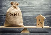 Money Bag With The Word Rent And A Wooden House On The Scales. The Concept Of Payment For Rental Hou poster