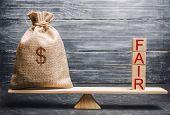 Money Bag And Wooden Blocks With The Word Fair. Balance. Fair Value Pricing, Money Debt. Fair Deal.  poster