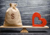 Bag With Money And Red Wooden Heart On The Scales. Money Versus Love Concept. Passion Versus Profit. poster