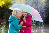 Kids With Colorful Umbrella Playing In Autumn Shower Rain. Little Boy And Girl In Warm Duffle Coat P poster