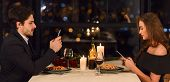 Man And Woman Do Not Communicate To Each Other And Using Their Smartphones During Dinner. Lack Of Co poster