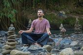 Man Meditating Yoga Lotus Pose Around Zen Stones. Travel Lifestyle Relaxation Emotional Concept, Sum poster