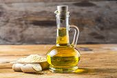 Sesame Seeds And Bottle With Oil On A Old Wooden Table,sesame Oil Oil In A Glass Jug. poster