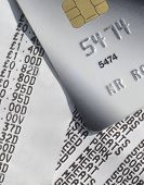 Closeup of credit card resting on supermarket till receipts