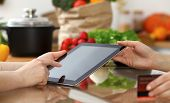 Close-up Of Human Hands Using Tablet Or Touch Pad. Two Women In Kitchen. Cooking, Friendship Or Onli poster