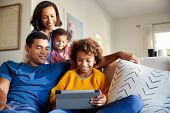 Young family spending time together using a tablet computer in their living room, front view poster