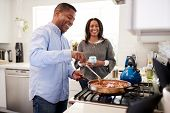 Millennial Hispanic man standing in the kitchen cooking with his partner standing beside him, backli poster