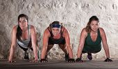 stock photo of lady boots  - Sweating women doing push ups during bootcamp workout - JPG