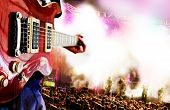 image of pop star  - Live music background.Guitar player and public in live
