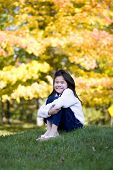 Image of little girl hugging knees sitting on lawn, autumn.