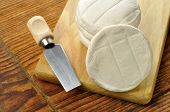 image of tomas  - Italian tomino cheese on a wooden chopping board italian appetizer - JPG