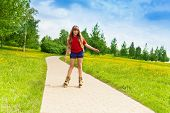 stock photo of scat  - Blond happy little 10 years old girl scatting in the park