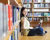 Portrait of a young smiling student using her laptop in a library