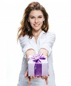 stock photo of gift wrapped  - sincere girl of european appearance in a white shirt giving a gift  - JPG