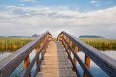 stock photo of bridge  - wooden bridge through river in morning sunlight - JPG