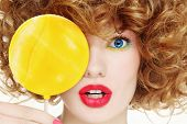 Close-up portrait of young beautiful woman with bright make-up and big yellow lollipop