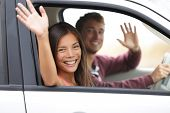 Drivers driving in car waving happy at camera. Young couple on road trip in new car. Interracial hap