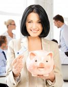 business and money saving concept - woman with piggy bank and cash money