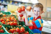 child boy during shopping with red ripe tomato vegetables at supermarket