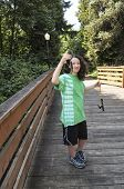 stock photo of brook trout  - Vertical photo of young girl looking at small trout while fishing off of wooden bridge for trout with walk path and trees in background - JPG