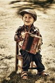 stock photo of newsboy  - Happy young boy playing accordion in summer