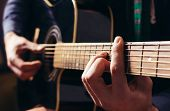 stock photo of guitar  - Man playing music at black wooden acoustic guitar - JPG