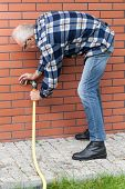 pic of spigot  - Vertical view of a elderly man repairing leaky garden hose spigot - JPG