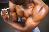stock photo of shirtless  - Close up of shirtless muscular man injecting steroids in the gym - JPG