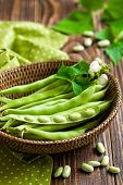 stock photo of bean-pod  - Green beans in a basket on a wooden table - JPG