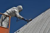 stock photo of cherry-picker  - Tradesman spray painting the roof of an industrial building - JPG