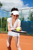 foto of youg  - Youg pretty giel playing tennis on cort - JPG