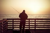 stock photo of early-man  - Fishing in the ocean from a pier in early morning - JPG