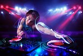 picture of disc jockey  - Handsome disc jockey playing music with light beam effects on stage - JPG