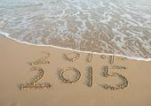 stock photo of calendar 2014  - new year 2015 written in sand - JPG