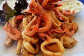 stock photo of squid  - Delicate fish fillets and sea foods such as shrimp and squid fried in deep fat - JPG