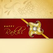 picture of rakhi  - Shiny golden rakhi on floral decorated maroon and beige background for Happy Raksha Bandhan celebrations - JPG