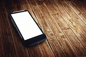 foto of generic  - Generic mobile smart phone with blank white screen on wooden table - JPG