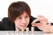 stock photo of japanese coin  - Businessman Put Coins To Stack Of Coins - JPG