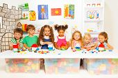 stock photo of school building  - Group of happy kids playing with blocks in kindergarten class constructing simple houses - JPG