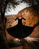 picture of levitation  - Young woman in black dress levitating in the forest - JPG