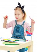 pic of montessori school  - Charming little girl draws with markers while sitting at table - JPG